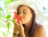 Woman smelling flower in park